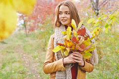 Girl with bunch of leaves Royalty Free Stock Photos