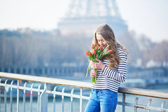 Girl with bunch of red tulips near the Eiffel tower Royalty Free Stock Photos