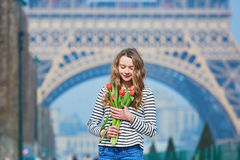 Girl with bunch of red tulips near the Eiffel tower Stock Images