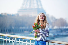 Girl with bunch of red tulips near the Eiffel tower Royalty Free Stock Photo