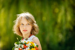 Girl with bunch of wildflowers outdoors Stock Photography