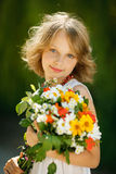 Girl with bunch of wildflowers outdoors Royalty Free Stock Photos