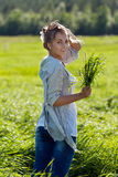 Girl with a bundle of green grass Royalty Free Stock Images