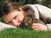 Girl with bunny. Girl with pet rabbit lie in the sun on the grass Royalty Free Stock Image