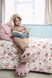 Girl In Bunny Costume And Monster Slippers Reading Book On Bed Stock Photo
