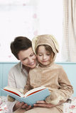 Girl Bunny With Mother Reading In Bed Stock Photos