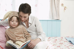 Girl Bunny With Mother Reading In Bed Royalty Free Stock Photos