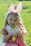 Girl with bunny wearing ears at spring green grass Stock Photo