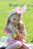 Girl with bunny wearing ears at spring green grass Stock Photos