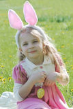 Girl with bunny wearing ears at spring green grass Royalty Free Stock Photography