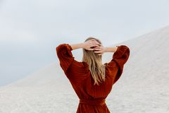 Girl in burgundy color blouse on a white sand brach. Back side view stock photography