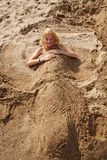 Girl buried under sand Royalty Free Stock Photos