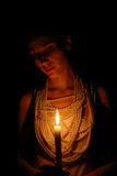 Girl with burning candle in darkness. Girl with burning candle and pearl necklace in the dark Royalty Free Stock Images
