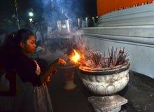 Girl burning incense at temple Royalty Free Stock Photos