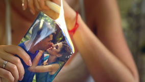 Girl burns photo with her boyfriend. stock footage
