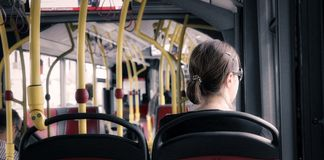 Girl on Bus. Young millennial woman sitting in public transportation Bus looking through Window Royalty Free Stock Photography