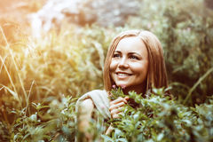 The girl in the bushes happy. Beautiful girl with on the background of the Bush. The girl smiles and looks thoughtfully to the side. Bush with little flowers on Royalty Free Stock Photography