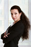 Girl in business clothes is standing sideways with arms crossed Royalty Free Stock Photo