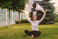 Girl in business office clothes sitting on grass. Throwing office documents or white sheets of paper royalty free stock photos