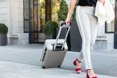 a girl in a business suit and glasses with a suitcase on the background of an expensive hotel. young beautiful woman eset luggage stock photo