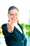 Girl in a business suit showing gesture - victory hand Stock Image
