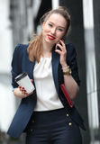 Girl in business suit talking on a cell phone Royalty Free Stock Image