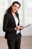 Girl in business suit writing in a document folder Stock Images