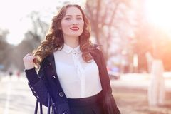 Girl business woman in the spring on a walk in a coat. Outdoor royalty free stock photo