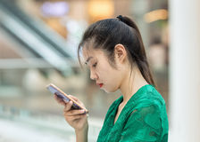 Girl busy with a smart phone in a shopping mall, Beijing, China. BEIJING-AUGUST 4, 2016. Girl busy with smart phone. China mobile internet market will exceed US$ royalty free stock image