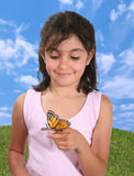 Girl and Butterfly. Cute girl looking at a butterfly on her finger royalty free stock images