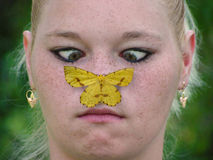 Girl and butterfly. Girl looking at butterfly on the tip of her nose Stock Photography