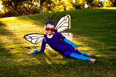 Girl In Butterfly Costume. A young girl dressed in a home made butterfly costume reclines on a hillside in a park Stock Image