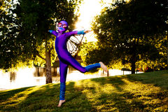 Girl In Butterfly Costume. A young girl dressed in a purple, butterfly costume leaps in a park as the late afternoon sun streams in behind her Stock Photos