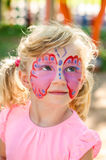 Girl with butterfly face painting. Beautiful blond girl with butterfly face painting stock images