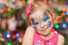Girl with butterfly face painting. Cute little Caucasian girl having butterfly painted on her face during children birthday party royalty free stock photos