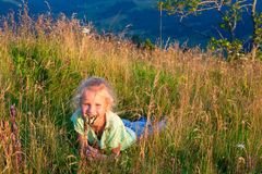 Girl and butterfly on mountain grasses Stock Images
