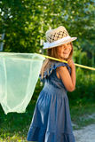 Girl with butterfly net. Happy beautiful girl with butterfly net at the sunshine royalty free stock photography