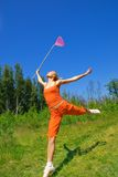 Girl with a butterfly net. Beautiful girl with a butterfly net jumping on a meadow Stock Image