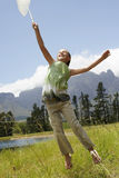 Girl With Butterfly Net Jumping In Field Stock Photo