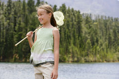 Girl With Butterfly Net Standing By Lake Stock Photography
