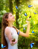 Girl with butterfly in summer forest Stock Photo