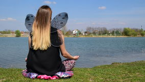 Girl with butterfly wings meditating in lotus position next to the calm water stock video
