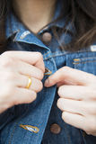 Girl is button up her Denim jacket. Wearing Stock Image