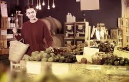 Girl buying artichokes Royalty Free Stock Photos