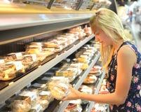 Girl buying cakes in supermarket royalty free stock photos