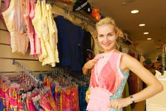 Girl buying clothes. Young beautiful girl buying clothes in a shop Royalty Free Stock Images