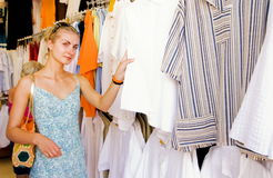 Girl buying clothes. Blond girl buying clothes in a shop Royalty Free Stock Photos