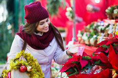 Girl buying floral compositions at Christmas fair Stock Photography