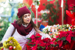 Girl buying floral compositions at Christmas fair Stock Photos