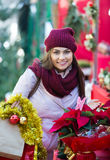 Girl buying floral compositions at Christmas fair Royalty Free Stock Photos